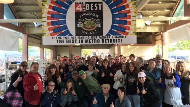 Market vendors and volunteers offer a thumbs-up thank you for helping make Farmington's farmers market the best in metro Detroit.