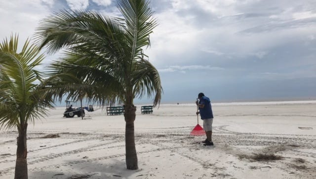 Crew rakes debris off stretch of Fort Myers Beach near the Outrigger resort on Wednesday. With some exceptions, Beach hotels ready to go when power is restored.