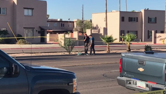 Police investigators stand near the wreckage of a bicycle that had been hit by a truck on Thomas Road near 46th Avenue in Phoenix. The bicyclist was pronounced dead at a hospital Sept. 20, 2017.