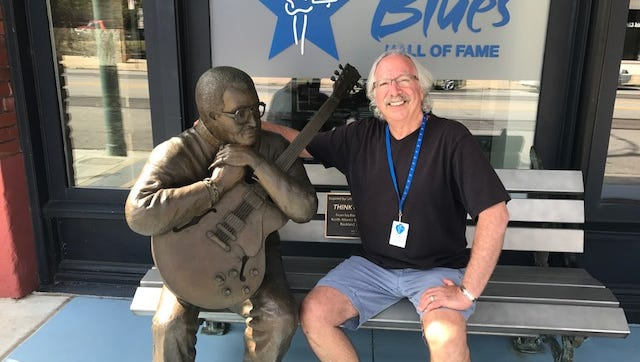 Retired Memphis lawyer Reed Malkin sits with the bronze icon of Little Milton in front of the Blues Hall of Fame on South Main Street. Malkin volunteers at the Hall of Fame.