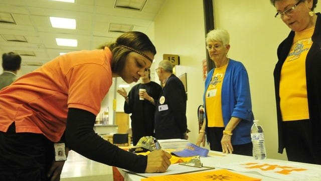 Susan Whitlow, center, and Jean Lusardi, right, gather signatures urging the University of Tennessee to restore the Lady Vols name and logo to all women's sports at the school.