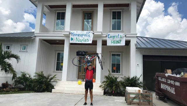 Heinz Ruch exults after arriving at his new home in Naples on Saturday. Starting out from Hastings, Minnesota, Swiss native Ruch bicycled from Minneapolis to Naples, raising money to provide hearing aids for those who cannot afford them.