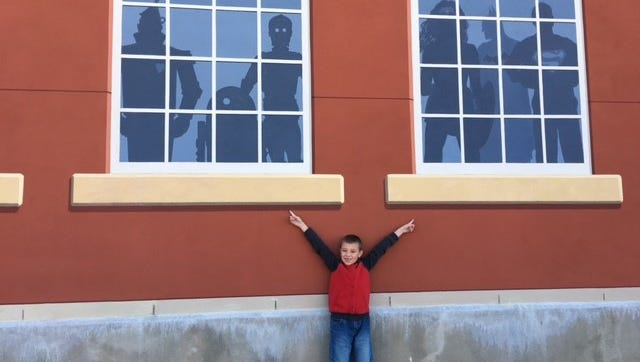 Eli Martin, 7, of Shelby, poses with his favorite movie 'Star Wars' characters painted as silhouettes in windows in a new mural in the Schines Art Park at South Sandusky Avenue and Warren Street. The outdoor movie park was dedicated Friday. Martin's grandparents Doug and Linda Godwin run the furniture store on the other side of the wall.