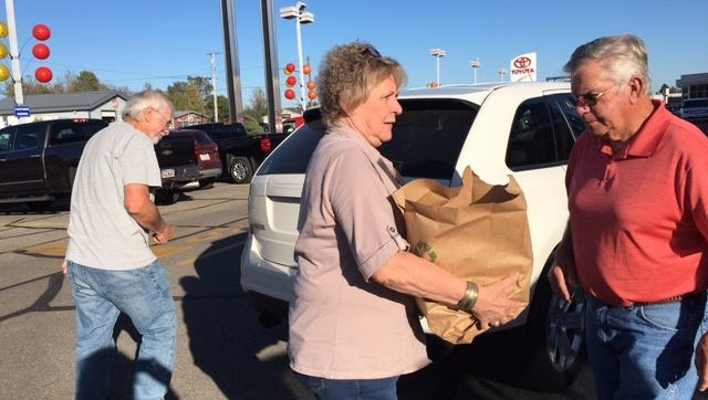 Bev and Walter Carpenter, right, volunteer at Make A Difference Day food drive at Graham Automall in this News Journal file photo.