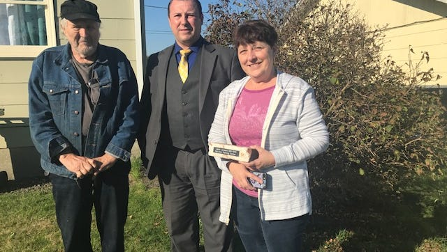 From left, Janie's father, Richard Landers, Detective Hinkle, Janie's sister, Joyce, with a memorial brick from Fairview presented by the Oregon State Police.