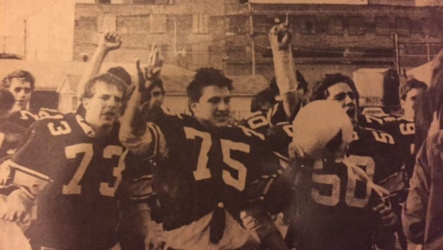 Goodrich High School players John Davis (no. 73), Dale Stahmann (75) and Mike King (50) leave Fruth Field with jubilant teammates after ending the 48-game winning streak of three-time defending WIAA Division 1 state champion Manitowoc in a quarterfinal playoff game on Oct. 31, 1987. The win before more than 5,000 fans propelled the Cardinals to their only WIAA state football title.