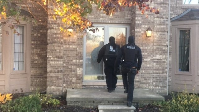 Authorities approach a Canton home to execute a search warrant amid a gang racketeering probe.