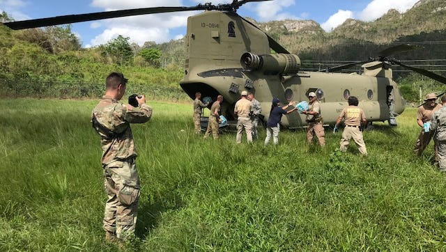 Pfc. William Dickinson, a public affairs broadcast specialist with the 24th Press Camp Headquarters, records members of the 1st Armored Division Combat Aviation Brigade and volunteers as they deliver food and water to Hurricane Maria survivors in Utuado, Puerto Rico.