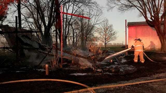 Greenfield Township Fire Department Lt. Ryan Smith sprays water on a collapsed barn Tuesday evening.