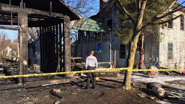 An investigator from the Ohio State Fire Marshal's Office Monday looks over the damage from a fire in Suphur Springs. No one was hurt in the early morning fire.