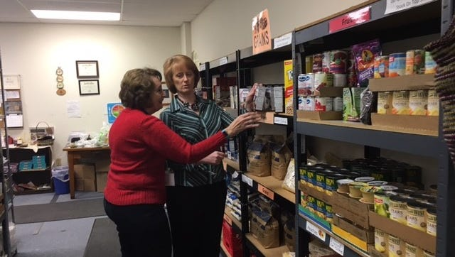 Rebecca Owens, director of Catholic Charities, at right, talks with volunteer Karen Amos in the food pantry Monday at their facility.