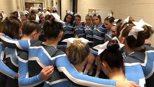 The Richmond High School cheer team huddles together Friday at Richmond High School.