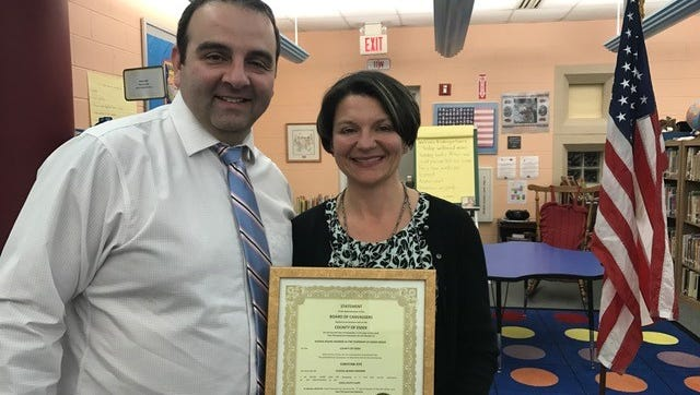 Cedar Grove Schools Business Administrator Michael Devita presents Board of Education President Christine Dye with her reelection certification on Jan. 2, 2018..