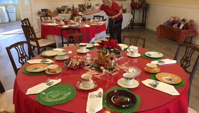 Pilot Club member Muriel Cowell assists with table decorations for the club's first annual holiday tea.