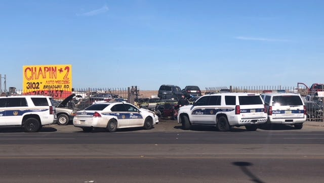 Phoenix police vehicles partially block the entrance to an auto salvage business where they were conducting a shooting investigation near 32nd Avenue and Broadway Road on Monday, Jan. 29, 2018.