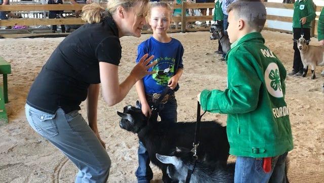 Karen Crawford, a National Pygmy Goat Association judge from Washington State, goes over showmanship with Jayden Black of Lakeland and Shelby Hollingsworth of Arcadia on Sunday.