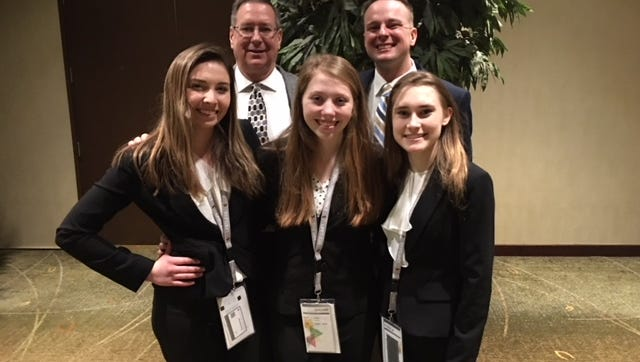 Advisers John Rasmussen and Josh Bauer stand with DECA competitors Ally O'Brien, Noelle Daniels and Katie Dusek at the 2018 state conference.