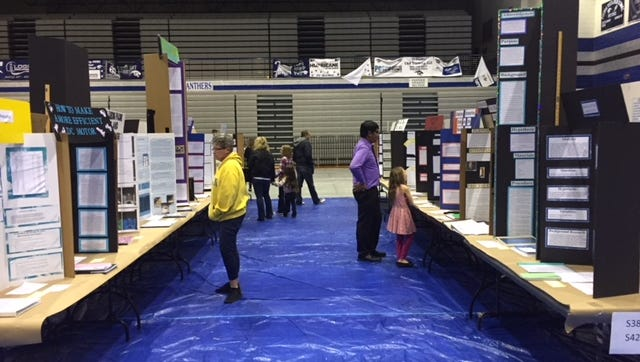 People browse science fair projects during the Regional Science Fair at Piedra Vista High School on Saturday.