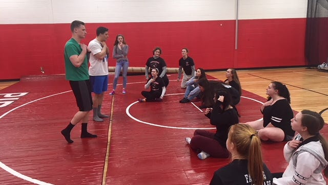 Cinnaminson police officers Garrett McLaverty (left) and Mark Berardis (right) give instruction to Cinnaminson High senior female students in a gym class. The two have taught the senior female students self-defense tactics twice per month since January in hopes of preparing them for possible physical attacks they could face in college or elsewhere.