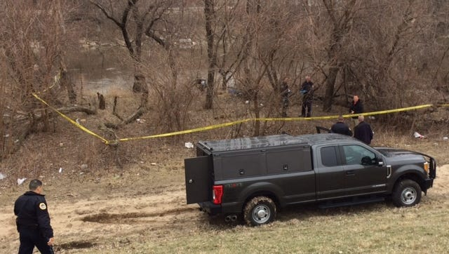 Police tape off the scene where a body was found near the river.