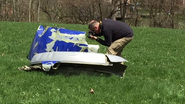 A federal agent photographs what is believed to be a piece of an engine that exploded on Southwest Airlines Flight 1380 on Tuesday. This piece is in Jefferson Township, Berks County.
