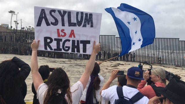 Central American migrants and supporters of the migrant caravan hold up signs from the U.S. side of the border looking south into Mexico on April 29, 2018.