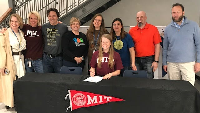 Ankeny resident Emily Larson is surrounded by her teachers and coaches as she signs her National Letter of Intent to play soccer at Massachusetts Institute of Technology (MIT) on Friday at Central Academy where she is a student.