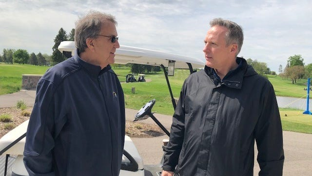 Former Michigan coach Lloyd Carr, left, and former Michigan quarterback Rich Hewlett talk during Monday's Swing to Cure Diabetes golf outing at Michigan.