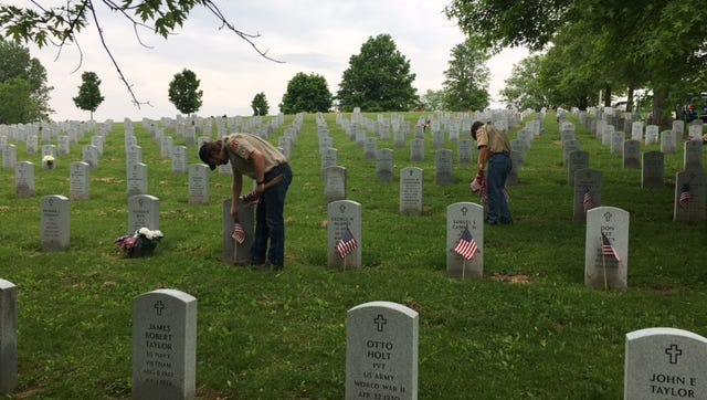 Volunteers flocked to Mansfield Cemetery Saturday to place U.S. flags on the graves of veterans.
