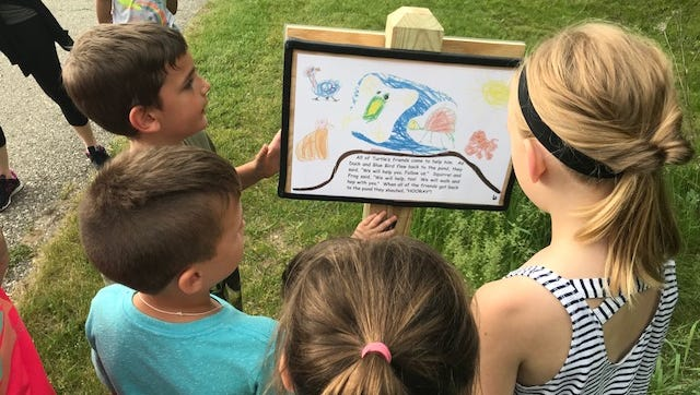 """Spencer Elementary students take turns reading """"Turtle Gets Lost"""" while on the story trail at Island Lake State Park Thursday May 31, 2018."""