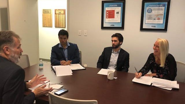 From left, Jerry Parrish, adjunct at Florida State University, discusses a study on Northwest Florida business incubators with graduate students Patrick Mas, Holt Johnson and Courtney Clark.