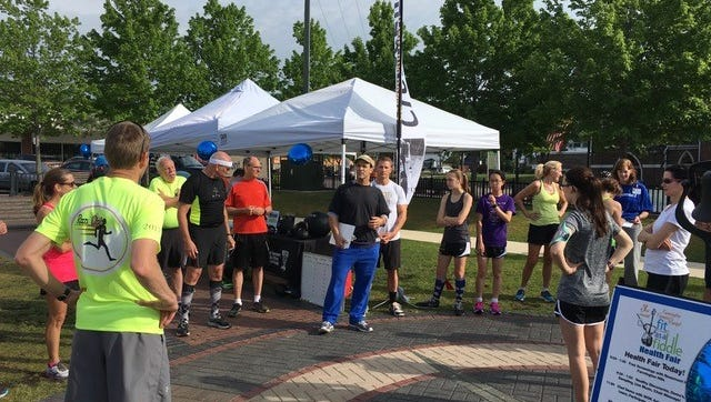 Dr. Joseph Williams of Farmington, along with Rick Smith (pictured behind), from Earned Not Given Crossfit prep runners for a 3.1 mile run through the streets of Farmington at the annual Fit as a Fiddle health fair.