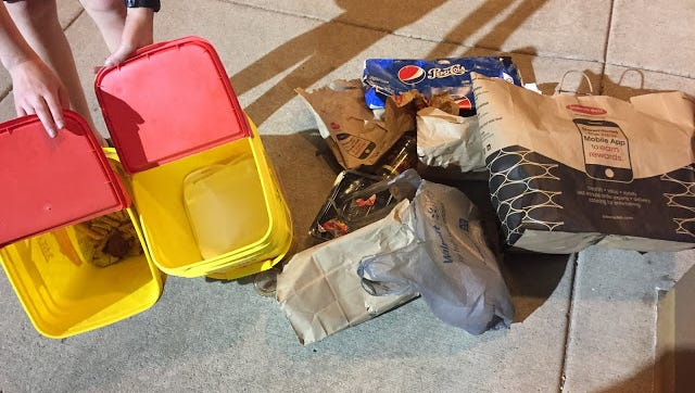 The Kendricks are planning to store their waste in the yellow containers on the left, which are cleaned out kitty litter bins. After just one day, they already have a hefty load of waste accumulated.