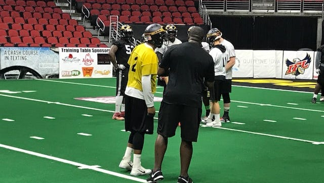 Iowa Barnstormers coach Dixie Wooten talks with quarterback Drew Powell during practice Thursday in Des Moines.