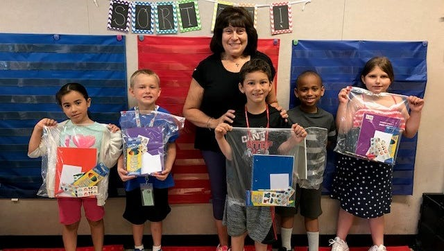 Linda Gallina, education chair, Woman's Club of Vineland, is joined by first graders from Jessica Hyland's class at Mennies Elementary School in Vineland. The club donated writing packets to Hyland's students to encourage them topractice their writing skills at home during thesummer break.