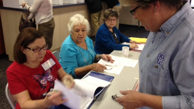 Poll worker Pat Dailey checks in voter Anne Richards at the Fort Mitchell poll location Lakeside Christian Church.