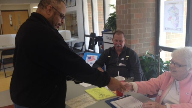 Robert Scotts hands his driver's license to poll worker Judy Klette at check-in in Union.