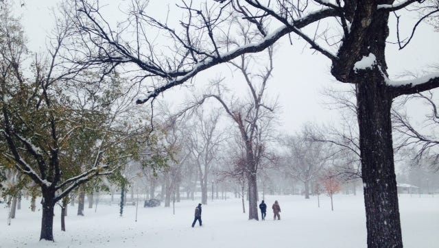 People walk through the snow at McKennan Park on Saturday morning.