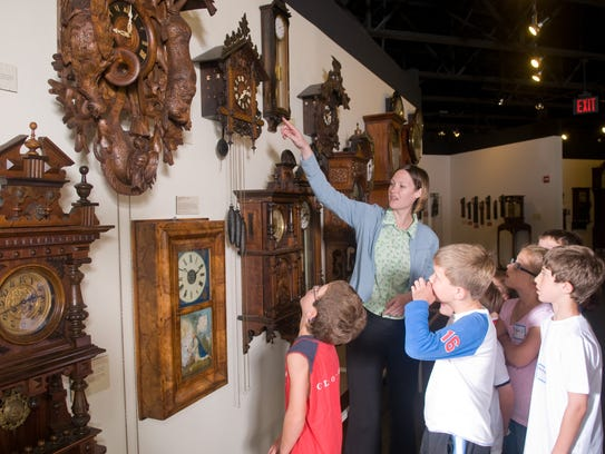 Young guests marvel at a wall of wooden clocks in the