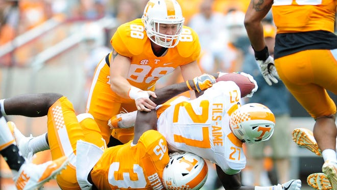 Tennessee running back Carlin Fils-aime (27) is tackled by defensive lineman Brandon Benedict (88) and linebacker Daniel Bituli (35) during the Orange & White Game at Neyland Stadium in Knoxville, Tennessee on Saturday, April 22, 2017.