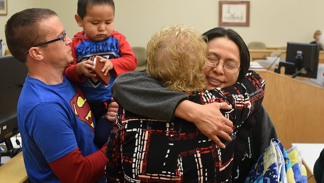 Rolanda Jeffrey, right, gets a hug after an adoption proceeding for her son on Friday at the Eleventh Judicial District Court in Farmington. At left are Randall Jeffrey and the couple's new son, Teddy.