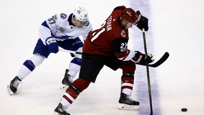 Arizona Coyotes center Derek Stepan (21) tries to keep the puck away from Tampa Bay Lightning center Yanni Gourde (37) during the second period of an NHL hockey game, Thursday, Dec. 14, 2017, in Glendale, Ariz. (AP Photo/Ross D. Franklin)