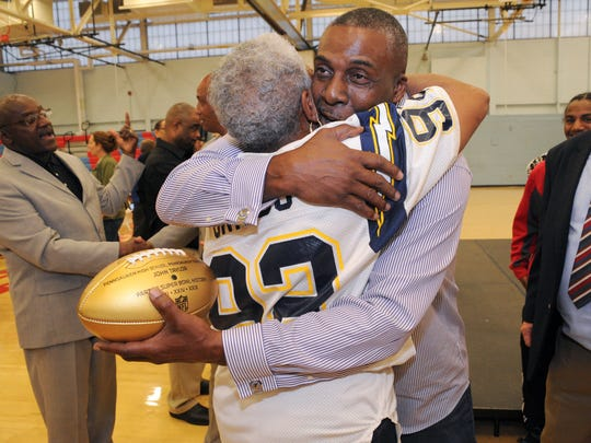 John Taylor, a three-time Super Bowl champion with the San Francisco 49ers and Pennsauken graduate of the class of 1980 hugs Hugs Griggs, mother of former NFL players David and Billy Griggs during a ceremony presenting the school with three gold footballs commemorating Super Bowl 50 on Friday. 5.13.16. Joe Warner/For the Courier-Post