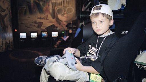 """In this May 1999 file photo, actor Jake Lloyd; who portrays young Anakin Skywalker in the film """"Star Wars Episode I: The Phantom Menace;"""" plays a game during the Electronic Entertainment Expo in Los Angeles. Colleton County Sheriffs Sgt. Kyle Strickland said Sunday, June 21, 2015, that deputies on Wednesday arrested a 26-year-old man they confirmed through a former talent agent Lloyd. Lloyd faces charges after leading South Carolina deputies on a high-speed chase."""