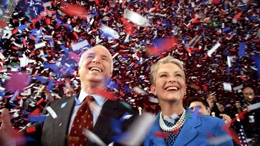 In this Jan. 30, 2000, file photo, then-Republican presidential candidate U.S. Sen. John McCain, R-Ariz., and his wife, Cindy, smile as confetti falls on them at the end of their 114th New Hampshire town hall meeting with voters at the Peterborough Town House in Peterborough, N.H. Peterborough was the sight of McCain's first town hall meeting in April 1999. It was the summer of 1999, and McCain didn't have many big names on the side of his campaign for president. He didn't have much money or decent crowds, and even resorted at one point to giving away ice cream to lure voters to an event.