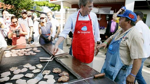 In this Aug. 14, 2015, file photo, Republican presidential candidate, former Florida Gov. Jeb Bush, talks with Dana Wanken, right, as he works the grill in the Iowa Pork Producers tent during a visit to the Iowa State Fair in Des Moines, Iowa.