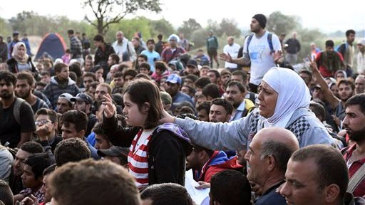 Refugees and migrants wait to pass the borders from the northern Greek village of Idomeni, to southern Macedonia in this September photo.