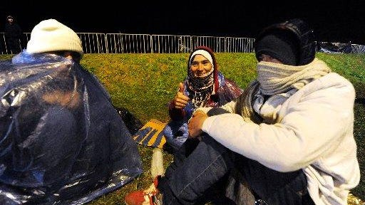 A person flashes a thumbs up as they wait along with some 200 migrants and refugees at the Bregana-Obrezje border crossing in Croatia on Monday, October 19, 2015 for Slovenian police to let them enter the country. Slovenian authorities said on October 19 that they had refused to let in more than 1,000 migrants arriving from Croatia after a daily quota had been reached, stoking fears of a new human bottleneck on the western Balkan route.