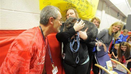 Science/media specialist Terry Schneider kisses Dillon, a one year-old pig, Wednesday after students read 5,500 books at Alameda Early Childhood Preschool in Farmington Hills, Mich.