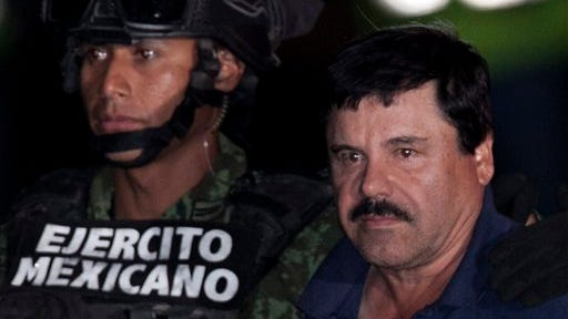 """Mexican drug lord Joaquin """"El Chapo"""" Guzman, right, is escorted by soldiers and marines to a waiting helicopter at a federal hangar in Mexico City in this file photo. Mexican authorities captured Guzman in January 2016 and he was extradited to the United States in January 2017."""